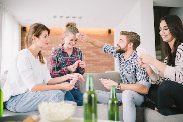 Rire des amis jouer aux cartes à la maison