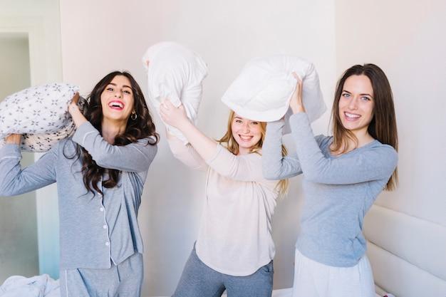 Rire des amis avec des oreillers