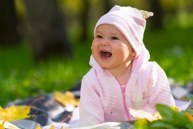 Rire bébé fille avec un large sourire rayonnant jouant sur une couverture sur l'herbe dans un parc d'automne dans un portrait candide