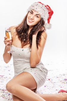 Rire belle jeune femme au chapeau de père noël et avec une coupe de champagne à la main. verticale. blanc .