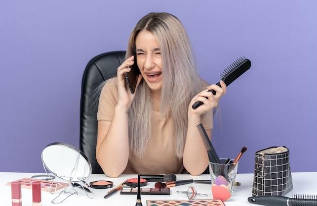 Rire belle jeune fille portant un appareil dentaire est assise à table avec des outils de maquillage parle au téléphone tenant un peigne isolé sur un mur bleu