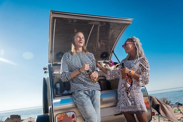 Rire et bière. élégant couple moderne se sentant détendu en riant et en buvant de la bière près de leur maison mobile