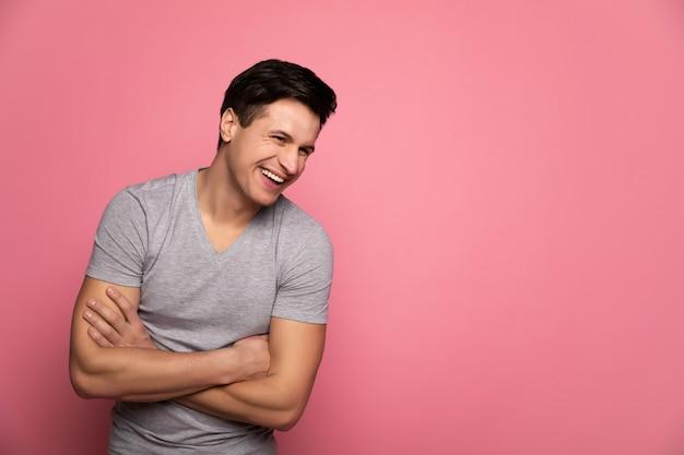 Rire d'une blague. homme heureux fort dans un t-shirt gris, qui rit les bras croisés.