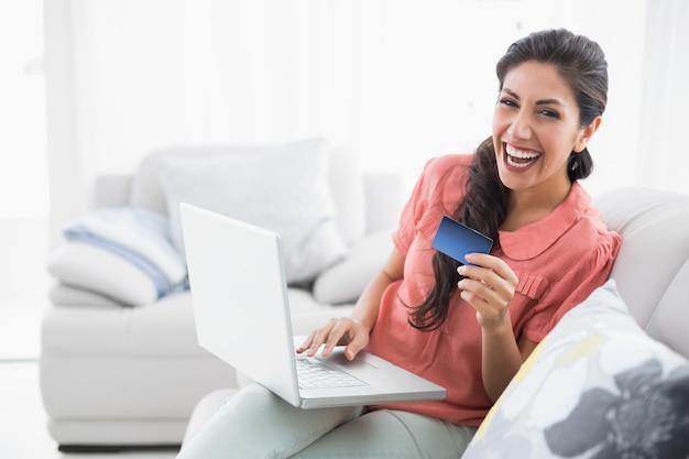 Rire brune assise sur son canapé en utilisant un ordinateur portable pour magasiner en ligne