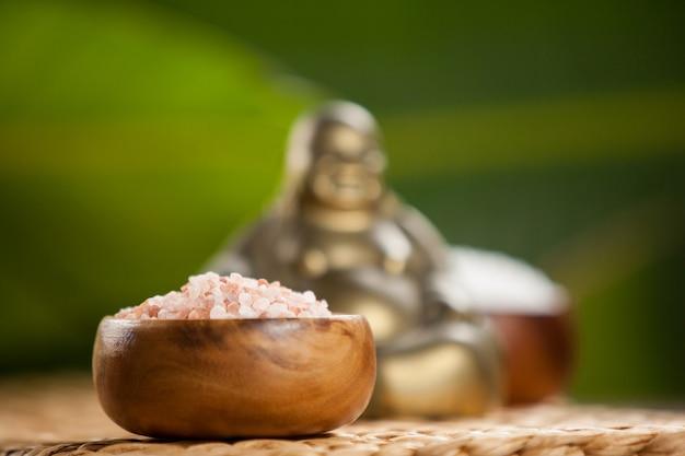Rire buddha figurine et le sel de mer dans un bol en bois