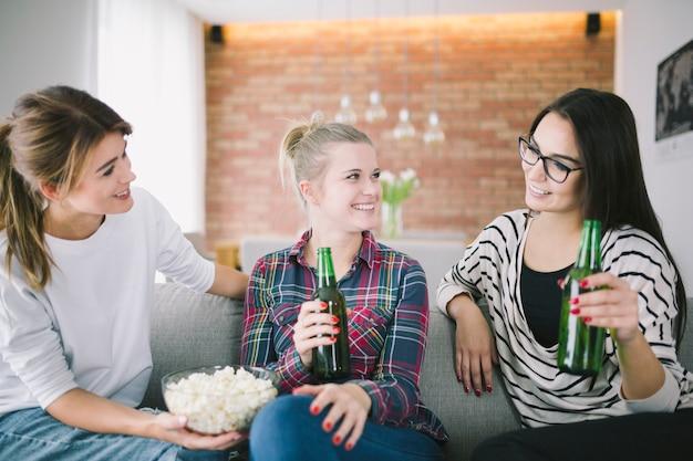 Rire des copines ayant de la bière à la maison