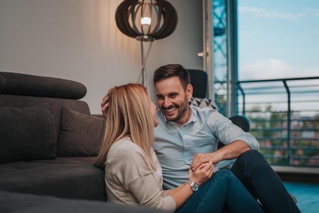 Rire couple assis sur le sol à la maison. profitez de passer du temps ensemble.