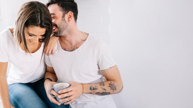 Rire couple communiquant au petit-déjeuner