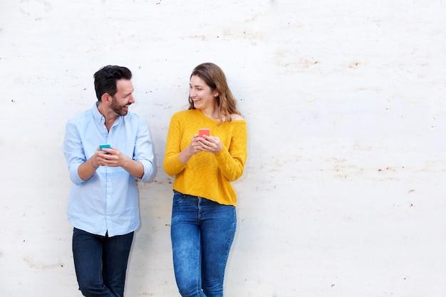 Rire couple debout par un mur blanc tenant des téléphones mobiles