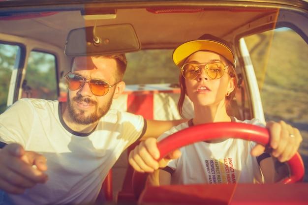 Rire couple romantique assis dans la voiture lors d'un voyage sur la route au jour d'été