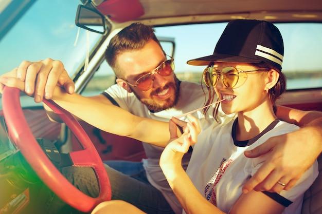 Rire couple romantique assis dans la voiture lors d'un voyage sur la route