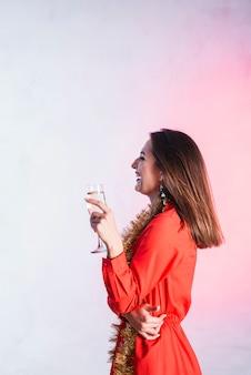 Rire dame en robe rouge avec flûte de champagne