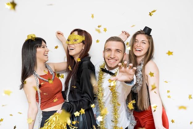 Rire dames et gars en tenue de soirée entre confettis d'ornement