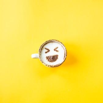 Le rire d'emoji est dessiné sur une tasse de café cappuccino