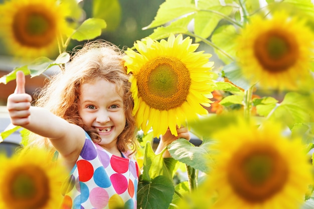 Rire enfant avec tournesol, montrant les pouces vers le haut.