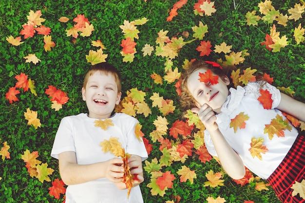 Rire des enfants allongés dans l'herbe jetant les feuilles d'automne dans l'air et montrant les pouces vers le haut.