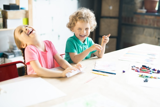 Rire d'enfants dessinant à table