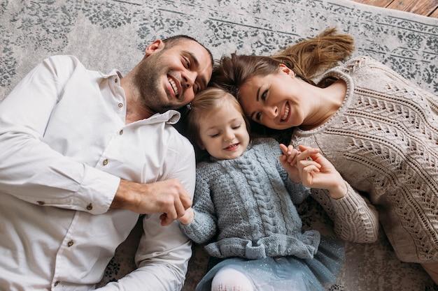 Rire de famille à la maison allongé sur le sol