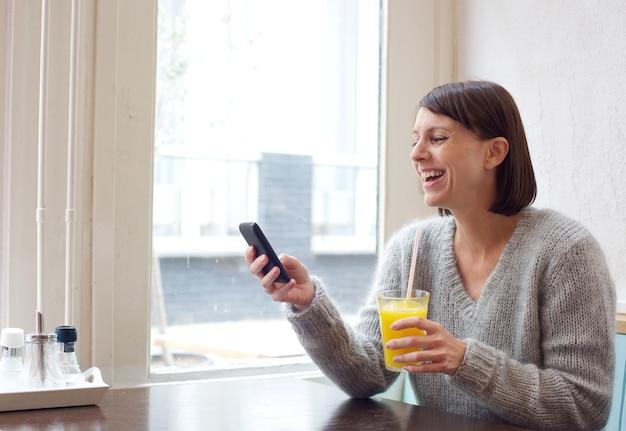 Rire femme assise au café avec téléphone portable