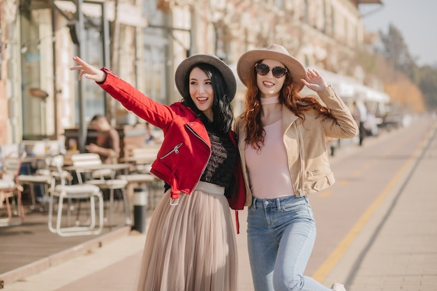 Rire femme brune montrant à un ami quelque chose d'intéressant