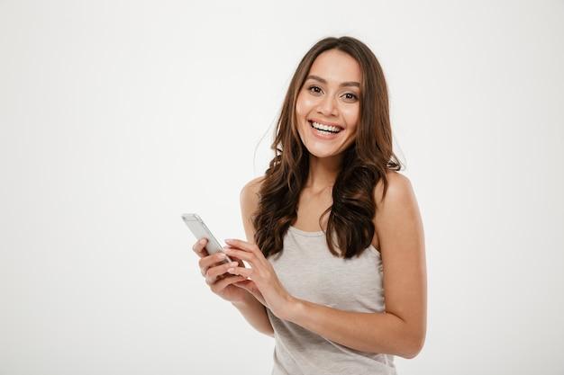 Rire femme brune tenant un smartphone et regardant la caméra sur gris