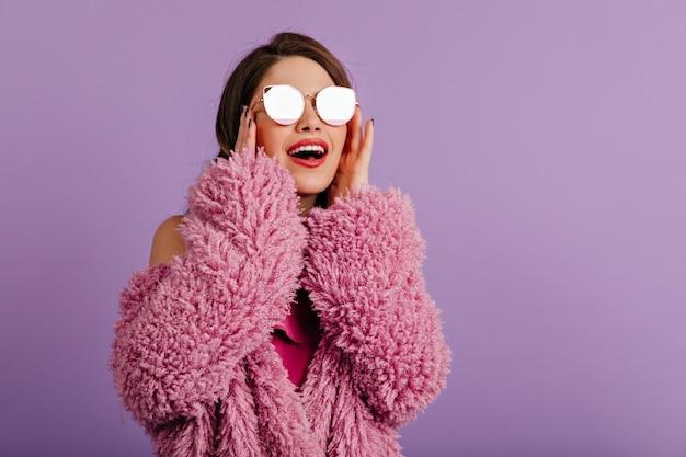 Rire femme brune toucher ses lunettes de soleil