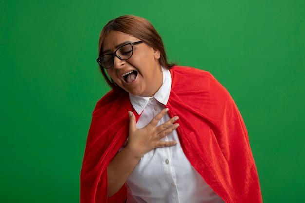 Rire femme de super-héros d'âge moyen portant des lunettes regardant vers le bas mettant la main sur la poitrine isolé sur fond vert