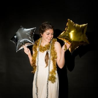 Rire femme en tenue de soirée avec des ballons