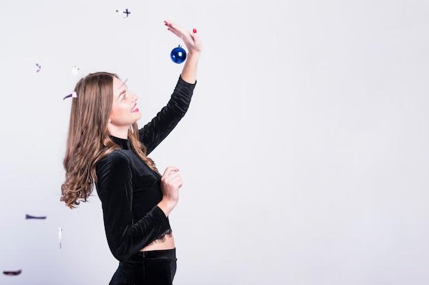 Rire femme en tenue de soirée avec boule de noël