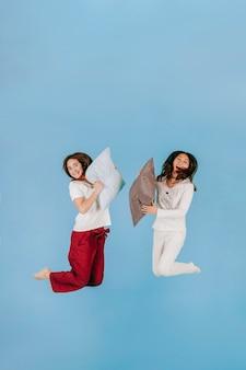 Rire des femmes sautant avec des oreillers