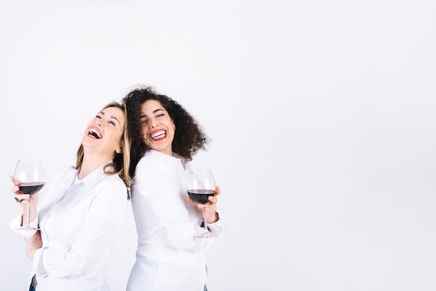 Rire des femmes avec des verres à vin