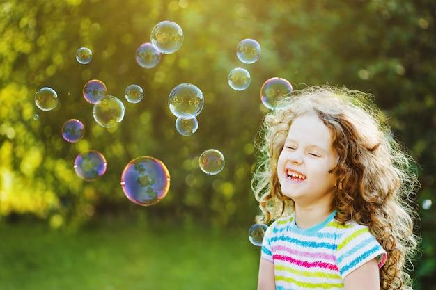 Rire fille bouclée avec des bulles.