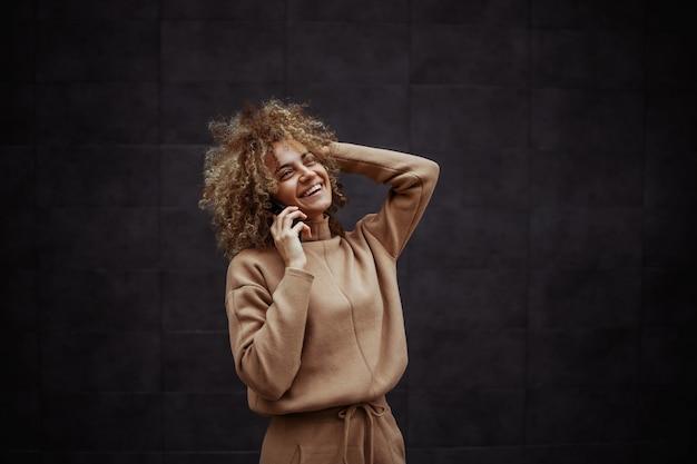 Rire fille hip hop en survêtement ayant un appel téléphonique avec son amie