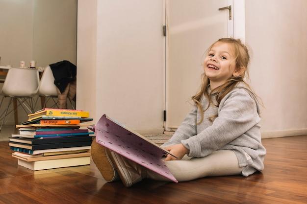 Rire fille lisant des livres sur le sol