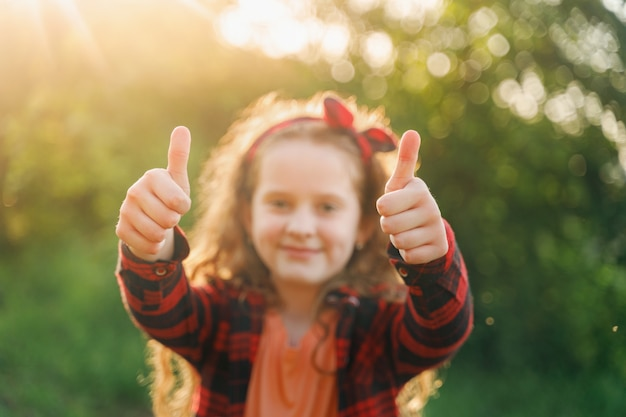 Rire fille montrant les pouces vers le haut.