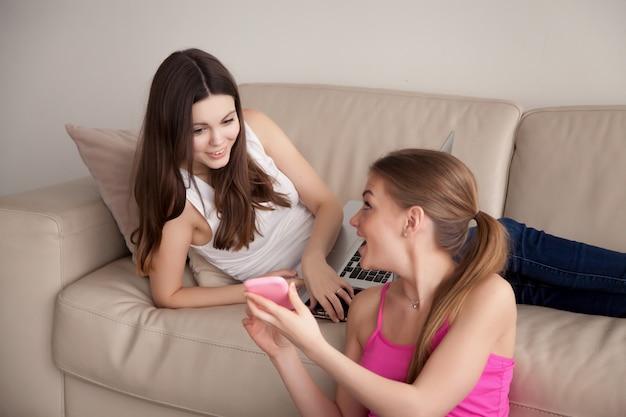 Rire fille montrant quelque chose de drôle sur smartphone à son ami