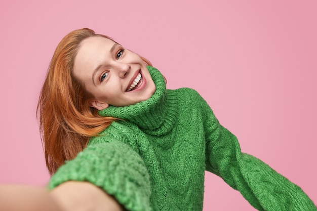 Rire fille prenant selfie sur fond rose