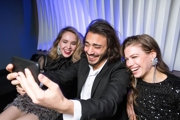 Rire filles glamour et homme élégant avec smartphone faisant selfie tout en profitant d'une fête en boîte de nuit