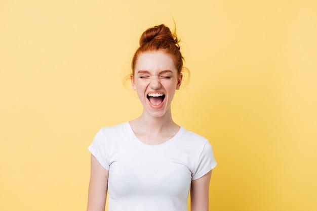 Rire gingembre femme en t-shirt avec les yeux fermés