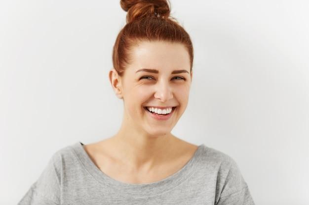 Rire à haute voix. gros coup de jolie jeune femme joyeuse portant ses cheveux roux en chignon plissant les yeux se moquant de quelque chose de drôle ou de ridicule tout en se relaxant à l'intérieur les gens et le style de vie