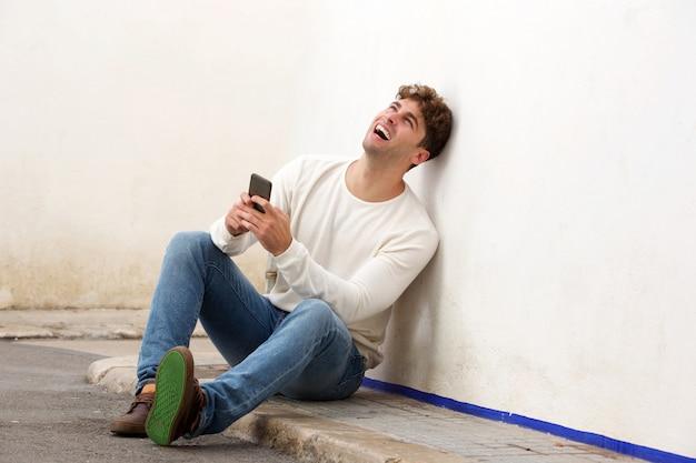 Rire homme assis sur le trottoir avec téléphone portable