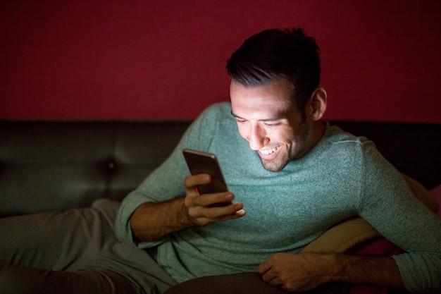 Rire, homme, utilisation, smartphone, sofa, nuit