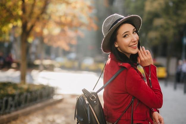 Rire incroyable femme au chapeau décontracté regardant par-dessus l'épaule sur le mur de la nature