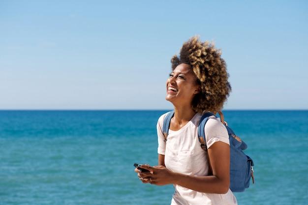 Rire jeune femme africaine sur la plage avec téléphone portable
