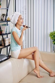 Rire jeune femme passer la soirée à la maison et enregistrer un message vocal pour un ami
