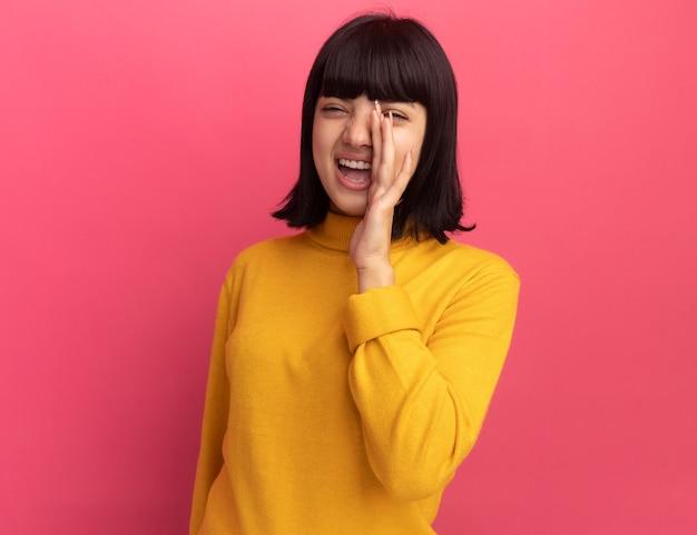 Rire jeune fille caucasienne brune tient la main près de la bouche rose