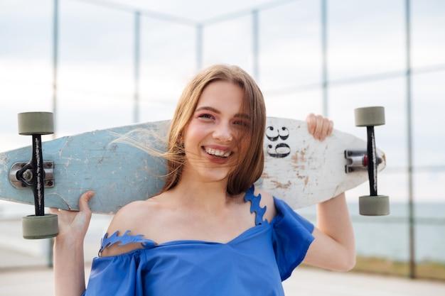 Rire jeune fille debout avec planche à roulettes à l'extérieur sur l'aire de jeux