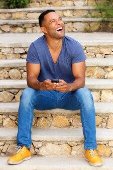 Rire jeune homme africain assis dans les escaliers en plein air avec un téléphone portable et en détournant les yeux