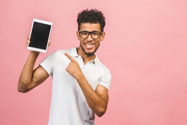 Rire jeune homme afro-américain tenant une tablette tactile
