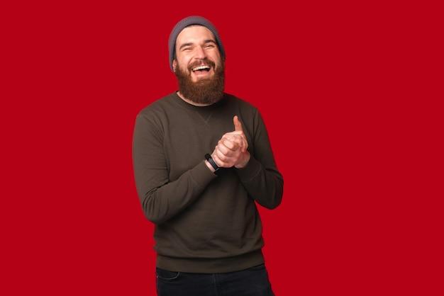 Rire jeune homme hipster barbu tient les mains ensemble.